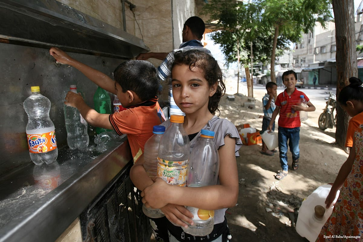 Palestinian children fill their bottles with water from a public tap in Gaza on 1 July, 2014 [Eyad Al Baba/Apaimages]