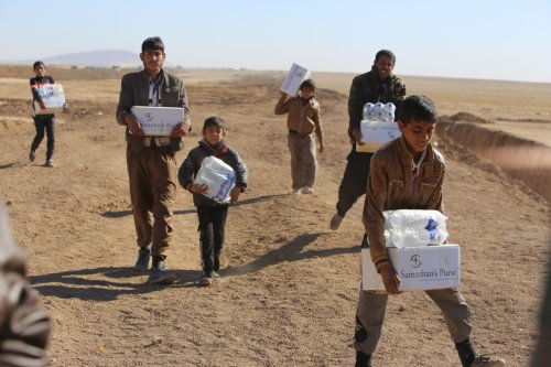 Internally relocated people, who fled their homes due to the clashes, receive food aid as they wait to be placed to refugee camps, at Omerkapci village of Bashiqa town in Mosul, Iraq on 20 November 2016 as the operation to liberate Iraq's Mosul from Daesh continues. [Feriq Fereç - Anadolu Agency]