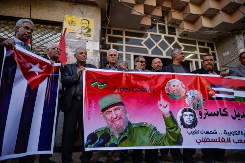 Palestinian People's Party supporters hold posters and National flag of Cuba during a commemoration ceremony of Fidel Castro in front of Shawwa Husary tower in Gaza on November 27th 2016 [Mustafa Hassona/Anadolu Agency]