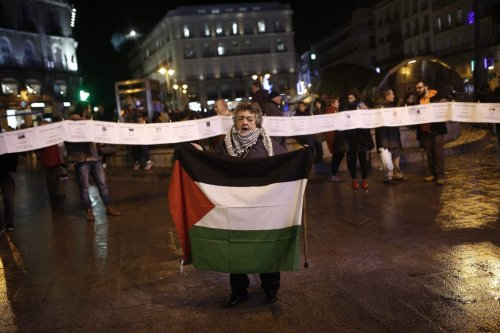 "People are seen with banners of Palestinians, who were killed by Israel, as protesters gather to stage a human chain protest in support of Palestinians during the ""International Day of Solidarity with the Palestinian People"" at Puerta del Sol, Madrid, Spain on November 29, 2016. ( Burak Akbulut - Anadolu Agency )"