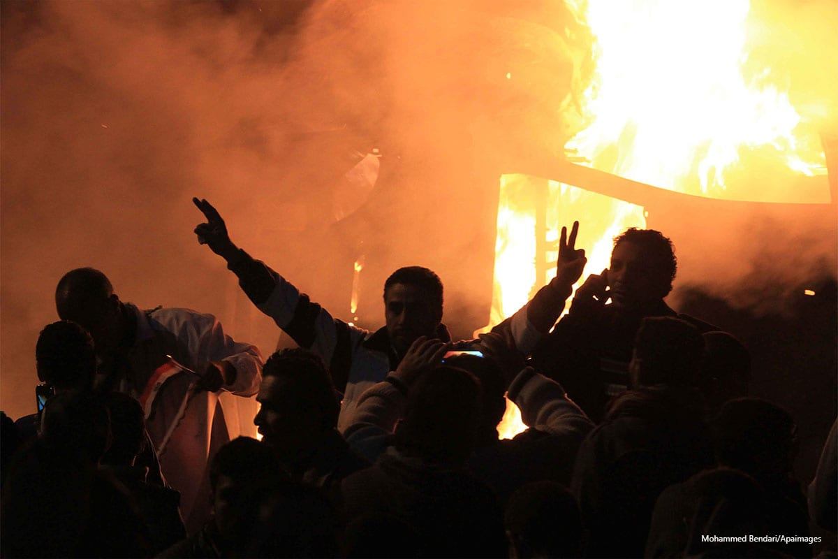 """Angry Egyptians set fire to a microbus after passengers allegedly held up four fingers, the symbol known as """"Rabaa"""" in Cairo on December 24 2013 [Mohammed Bendari/Apaimages]"""