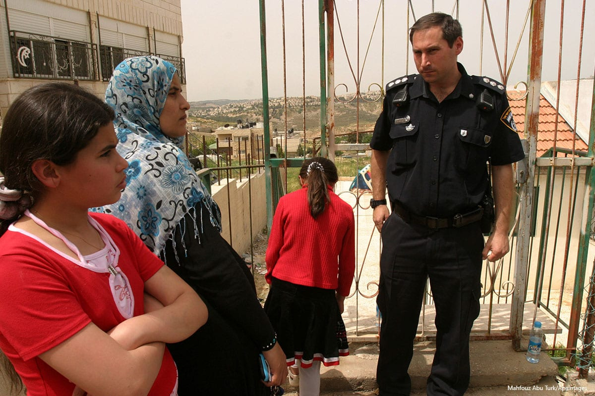 Israeli police stand guard at a Palestinian household as they are being forced to hand over their home to Jewish settlers in east Jerusalem on April 18 2012 [Mahfouz Abu Turk/Apaimages]