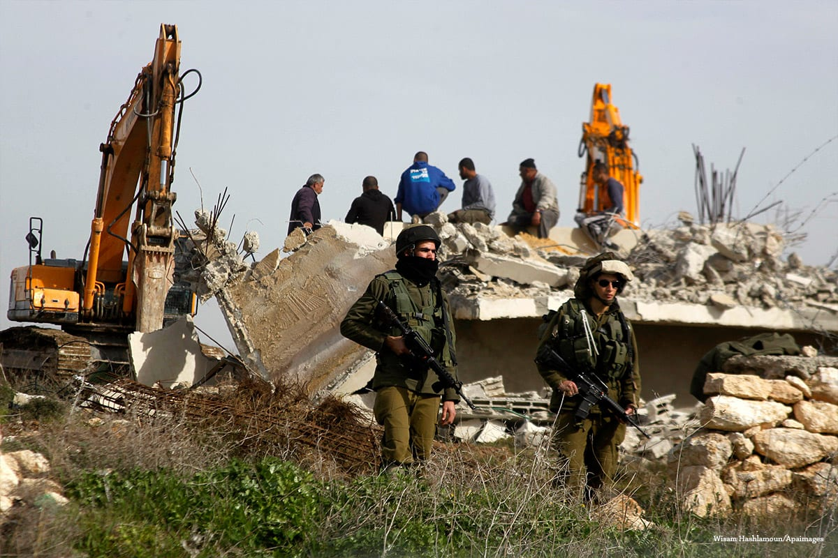 Israeli soldiers stand guard during the demolition of a Palestinian house at the order of the Israeli army in the West Bank on January 21 2016 [Wisam Hashlamoun/Apaimages]