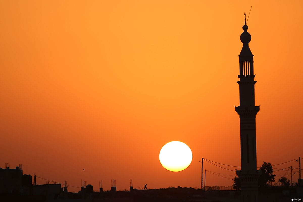 The sun sets behind the minaret of Hera' mosque, in Jalazoun refugee camp, near the West Bank city of Ramallah, on August 9, 2015 [Shadi Hatem / ApaImages]
