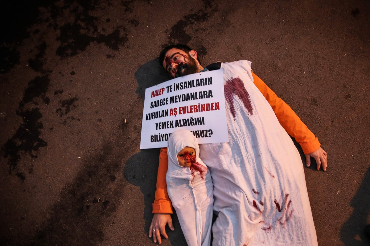 A protester with his mouth taped with black tape stages a show with a red painted shrouded doll, symbolizing murdered children and babies during a demonstration, condemning massacres and attacks in Syria's on 8 December, 2016 [Berk Özkan/Anadolu Agency]