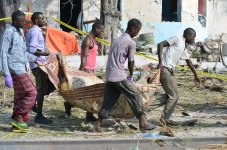 Security personnel remove the bodies of a car bomb attack victims near the port in the capital Mogadishu, Somalia, 11 December 2016 [Abdirizak Mohamud Tuuryare / Anadolu Agency]