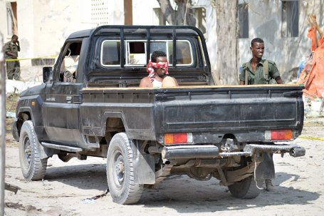 A suspect is seen behind a vehicle at the scene of a car bomb attack near the port in the capital Mogadishu, Somalia, 11 December 2016 [Abdirizak Mohamud Tuuryare / Anadolu Agency]