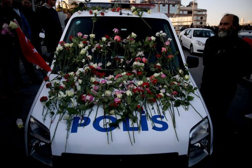 A police vehicle with flowers is seen as people gather for the victims of Istanbul terror attacks near the Vodafone Arena in Istanbul's Besiktas, Turkey on December 11, 2016 [Onur Çoban / Anadolu Agency]