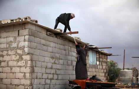 KHAN YUNIS, GAZA - DECEMBER 14: A man and a woman try to repair their roof as cold weather affects Khan Yunis in Gaza on December 14, 2016. ( Ashraf Amra - Anadolu Agency )