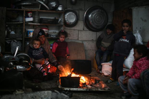 KHAN YUNIS, GAZA - DECEMBER 14: A Palestinian family is seen at their house as Palestinians living in makeshift homes in El-Zohor neighborhood in the city of Khan Yunis on the Gaza Strip are facing difficult conditions under the cold weather on December 14, 2016. The economy and their living conditions are getting progressively worse due to Israel's embargo on Gaza. ( Mustafa Hassona - Anadolu Agency )