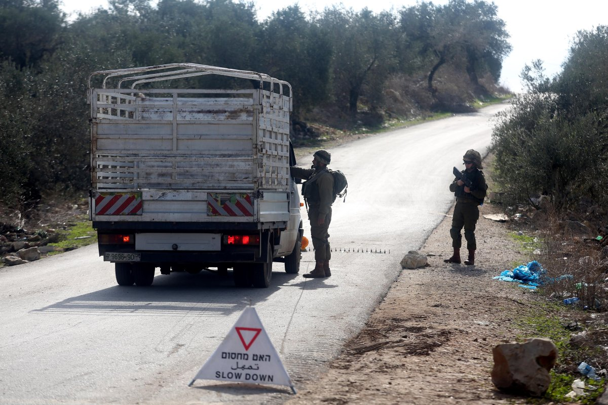 Israeli soldiers check vehicles at the entrance of Deir Abu Mash'al villiage during an operation carried out after opening fire to a Jewish in Ramallah, West Bank on December 19, 2016 [Issam Rimawi - Anadolu Agency]