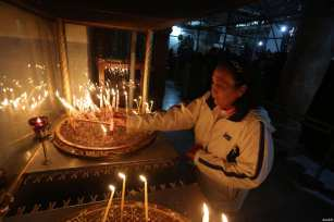 People light candles at the Church of the Nativity, which is traditionally considered to be located over the cave that marks the birthplace of Jesus, ahead of the Christmas in Bethlehem, West Bank on December 24, 2016 [Issam Rimawi / Anadolu Agency]