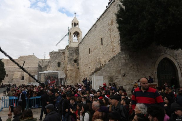 People watch Palestinian marching band's parade near the Church of the Nativity ahead of the Christmas in Bethlehem, West Bank on December 24, 2016 [Issam Rimawi / Anadolu Agency]