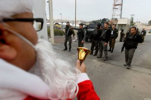 A Palestinian protestor dressed up as Santa Claus, demonstrates next to a gate at a section of Israel's separation wall in the biblical town of Bethlehem, in the occupied West Bank, on December 23, 2016 [Wisam Hashlamoun / ApaImages]