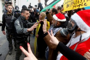 Palestinian protesters argue with Israeli border guard during clashes at a demonstration next to a section of Israel's separation wall in the biblical town of Bethlehem, in the occupied West Bank, on December 23, 2016 [Wisam Hashlamoun / ApaImages]