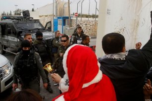 Palestinian protestors, some dressed up as Santa Claus, demonstrate next to a gate at a section of Israel's separation wall in the biblical town of Bethlehem, in the occupied West Bank, on December 23, 2016 [Wisam Hashlamoun / ApaImages]