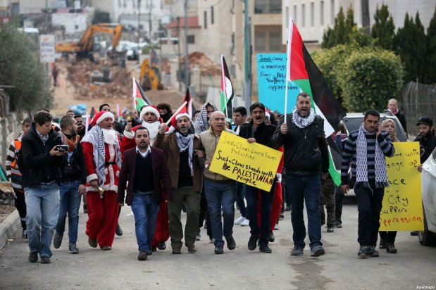 Palestinian demonstrators holding Palestinian flags take part in a protest next to a gate at a section of Israel's separation wall in the biblical town of Bethlehem, in the occupied West Bank, on December 23, 2016 [Wisam Hashlamoun / ApaImages]