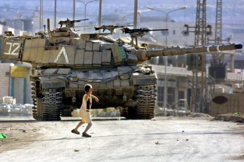 A Palestinian child throws stones at an Israeli tank, much like the iconic image of Faris Odeh from October 2000, during the First Intifada