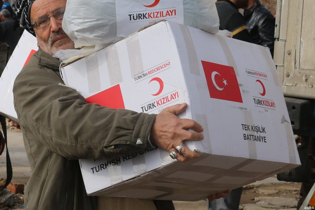 File photo of Turkmen people carry aid distributed by Turkish Red Crescent at the Bashir village in Kirkuk, Iraq on December 31, 2016 [Ali Mukarrem Garip / Anadolu Agency]