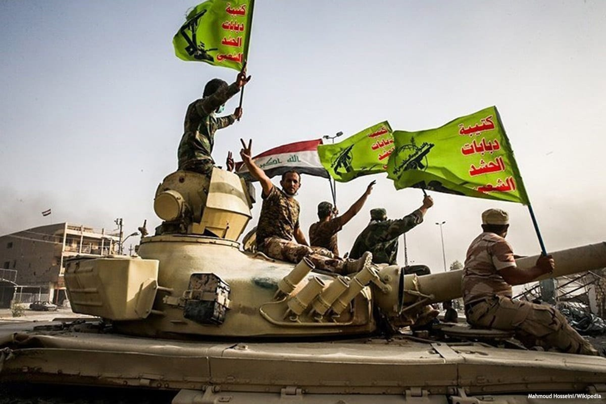 Image of militants raising the Iraq and Popular Mobilisation Forces (PMF) flag [Mahmoud Hosseini/Wikipedia]