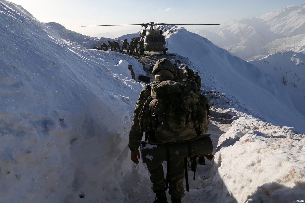 Turkish soldiers load cargoes into a military helicopter as others walk towards them in Hakkari, Turkey on 30 December 2016 [Özkan Bilgin/Anadolu Agency]