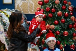 GAZA CITY, GAZA - JANUARY 5: Children are seen in front of a Christmas tree as people attend a celebration within Christmas preparations in Gaza City, Gaza on January 5, 2017. Orthodox Christians will celebrate the Christmas on January 6 according to Julian Calendar. ( Mohammed Asad - Anadolu Agency )