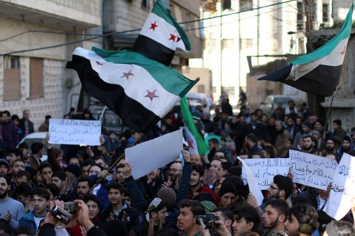 People holding flags and banners stage an anti-government protest after Friday Prayer at Merc town of Eastern Goutha in Damascus, Syria on January 6, 2017.