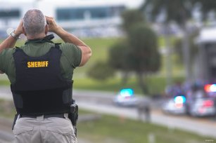 A Broward County sheriff's deputy stands on a highway entering Fort Lauderdale International Airport, using binoculars to look towards the airport on January 06, 2017 in Florida, USA.