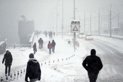 People walk snow covered Galata Bridge as heavy snowfall hits Istanbul, Turkey on January 9, 2017.