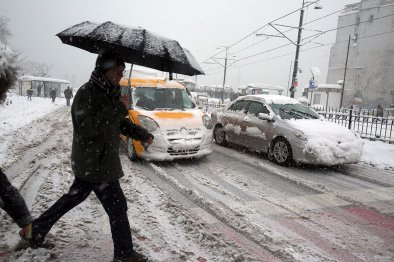 A man with an umbrella crossing over the road as heavy snowfall hits Istanbul, Turkey on January 9, 2017.