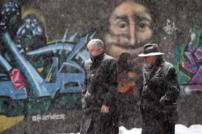 Two men walk past a wall with graffiti as heavy snowfall hits Istanbul, Turkey on January 9, 2017.