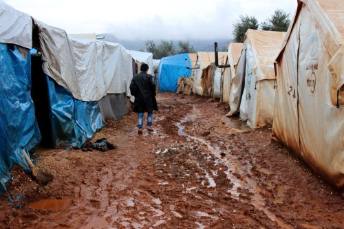 A Syrian kid walks over a muddy road between tents at the Refugee camp in Idlib, Syria on January 9 2017 [Abdulghani Arian/Anadolu Agency]