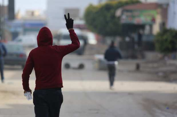 MEDENINE, TUNISIA - JANUARY 11: A protester flashes victory sign as the protesters demanding social rights to citizens and resolution of the crisis at Ras Jadir border crossing btween Libya and Tunisia, clash with the police in Ben Gardane town of Medenine, Tunisia on January 11, 2017. ( Tasnim Nasri - Anadolu Agency )