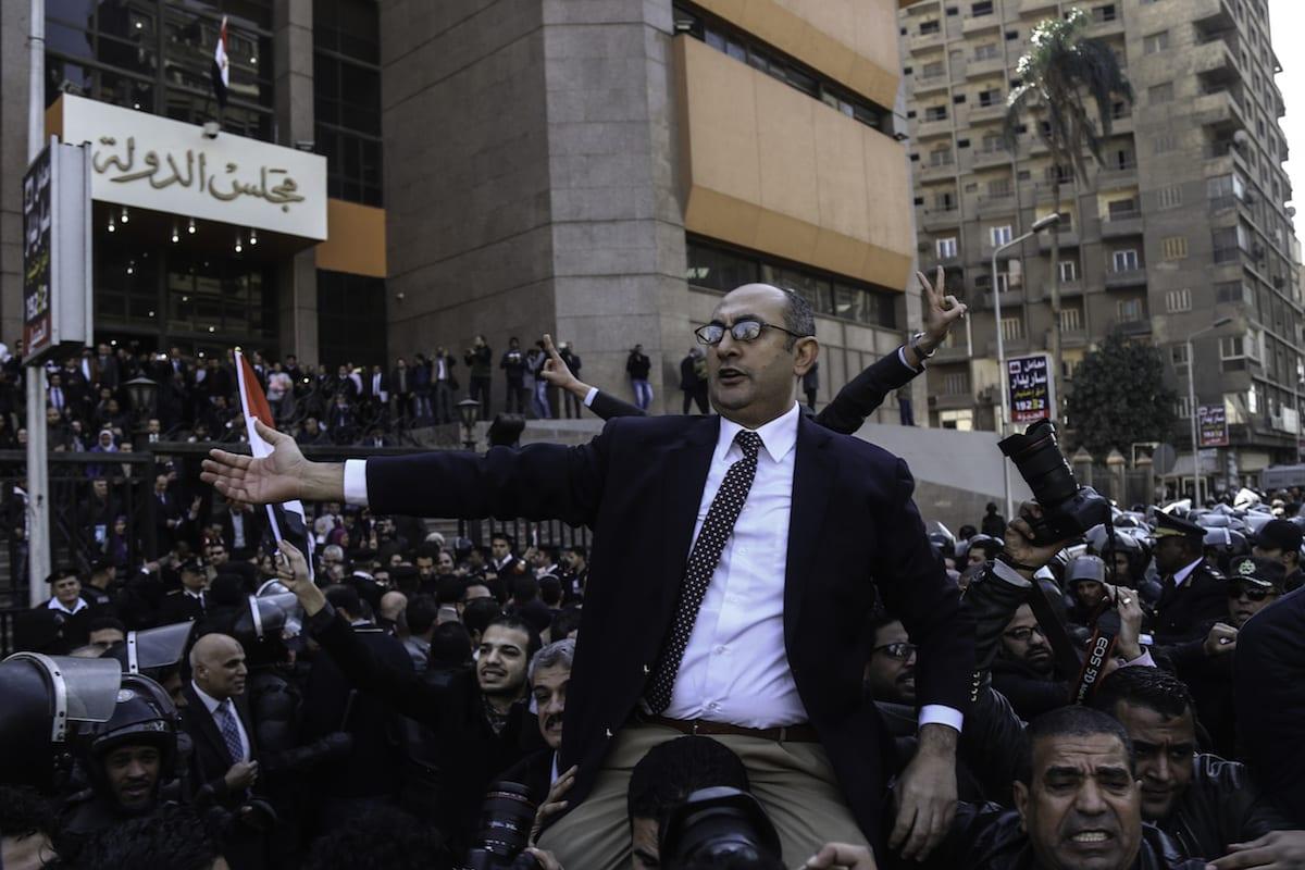 Egyptian lawyer Khaled Ali (C) celebrates amid street crowds after Supreme Administrative Court upheld for final session [Mohamed El Raai/Anadolu Agency]