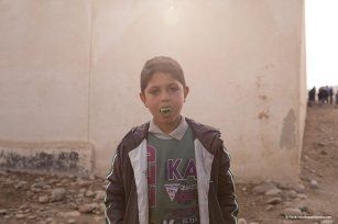 In Mosul, a mortar attack is launched less than half a mile away and within range. In the midst of the chaos a boy wearing a pair of luminous vampire teeth stops to see what I am up to [Ty Faruk/middleeastmonitor.com]