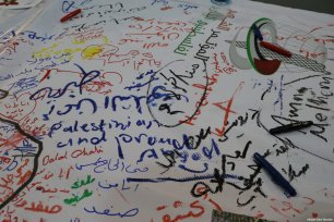 Delegates at the Palestinians Abroad conference write on the message wall in Istanbul, Turkey on February 25, 2017 [Middle East Monitor]