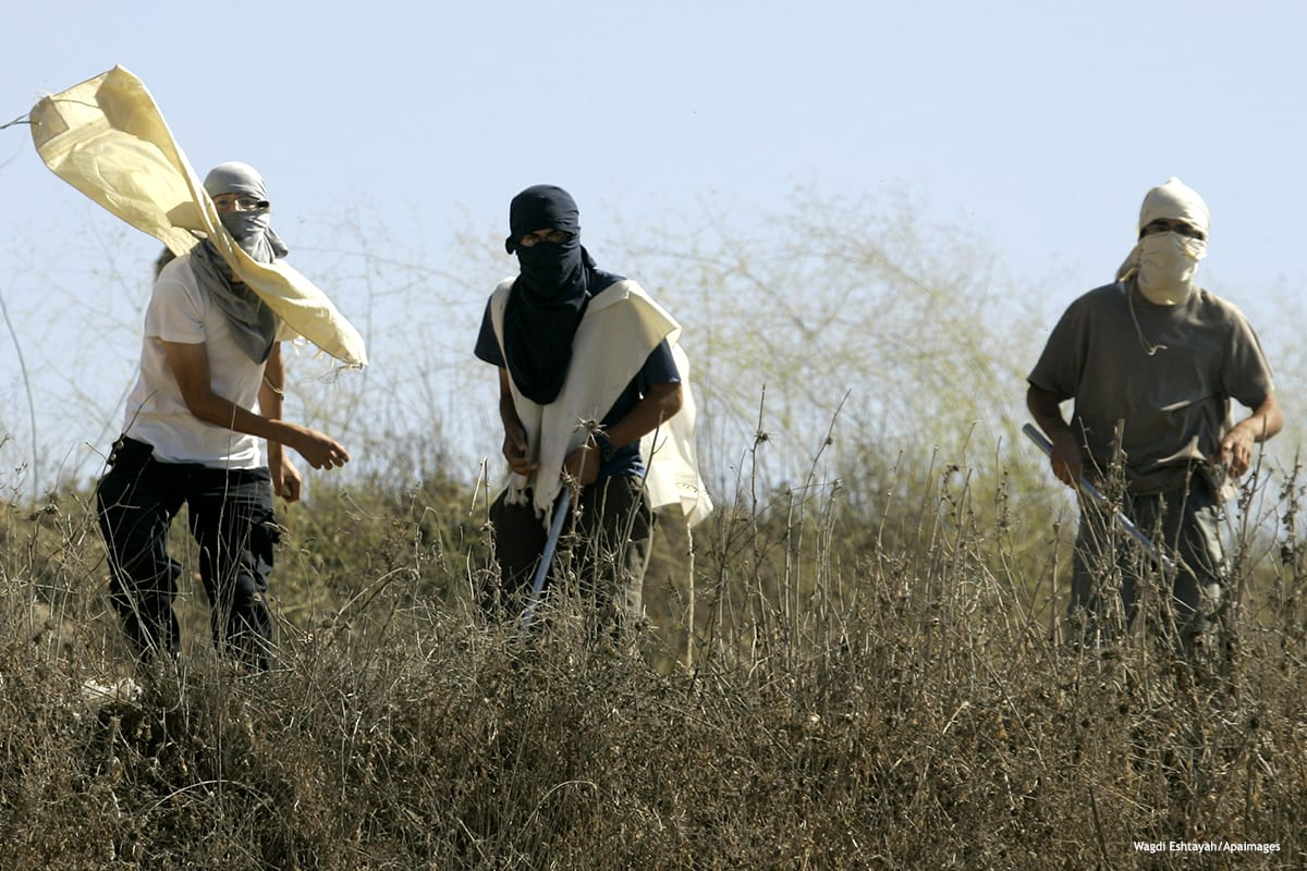 Image of masked Jewish settlers throwing stones toward Palestinians in the West Bank [Wagdi Eshtayah/Apaimages]