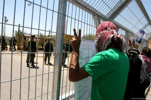 Palestinian protesters hold pictures of Palestinian prisoners outside of an Israeli prison [Issam Rimawi/Apaimages]