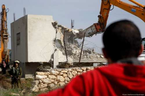 A Palestinian man sees the demolition of a Palestinian home at the order of the Israeli army in the West Bank village [Wisam Hashlamoun/Apaimages]