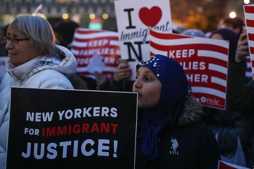 """A woman girl holds a sign reading in """"New Yorkers for Immigration Justice"""" during a rally in Foley square supporting immigration in New York City on February 1, 2017. ( Mohammed Elshamy - Anadolu Agency )"""