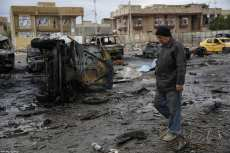 A man walks past the wreckage of cars a day after a car bomb attack at al-Bayaa auto gallery in capital of Baghdad, Iraq on February 17, 2017. Many casualities reported after the attack. ( Murthadha Sudani - Anadolu Agency )