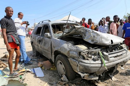 People inspect the damaged car after a bomb-laden vehicle attacked a marketplace in Moghadishu, Somalia on February 19, 2017 [Sadak Mohamed / Anadolu Agency]