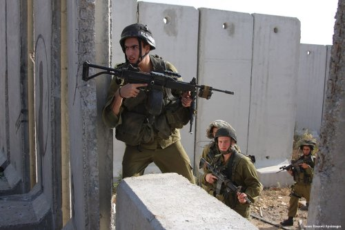 Israeli soldiers stand at the apartheid wall in Israel [Issam Rimawi/Apaimages]