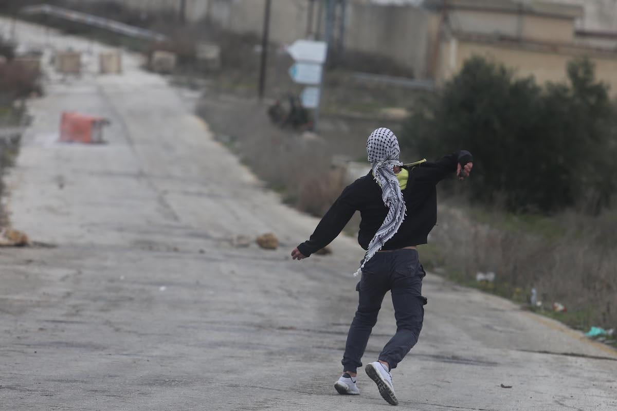 Palestinian students from Birzeit University, gathered near Beit Al Israeli settlement, sling stones to Israeli security forces as a response to their intervention during a protest demanding release of Palestinian prisoners from Israeli prisons, in Ramallah, West Bank on 1 March 2017 [Issam Rimawi - Anadolu Agency]