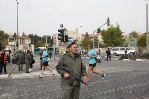 Israeli security forces stand guard as participants compete during the 7th annual International Jerusalem Marathon in Jerusalem on March 17, 2017 [Mostafa Alkharouf / Anadolu Agency]