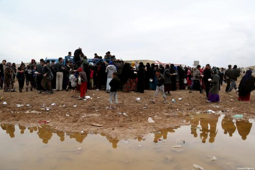 Iraqi civilians who fled from clashes between Iraqi Army and Daesh, queue up for food aid at the refugee camp in Hamam Ali town, as the operation to retake Iraq's Mosul from Daesh terrorists continues in Mosul, Iraq on March 19, 2017 [Yunus Keleş / Anadolu Agency]