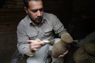 An archaeologist from Iraqi Kurdish Regional Government's Erbil Archaeology Department holds a skull found during an excavation work in Erbil, Iraq on March 21, 2017 (Hemn Baban/Anadolu Agency)