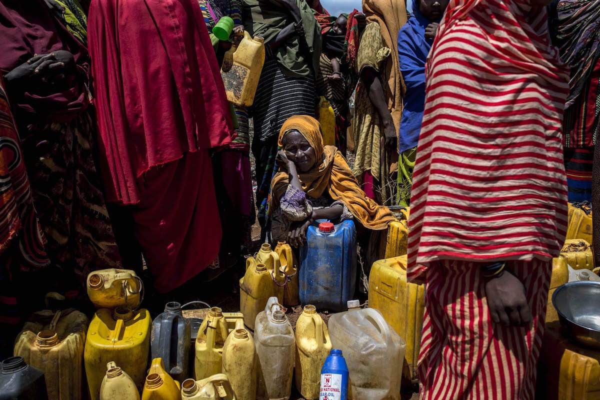Somalian woman fills up her plastic bottles with water at Dakamur camp in Somalia's Bay state on March 27, 2017. [Arif Hüdaverdi Yaman/Anadolu Agency ]