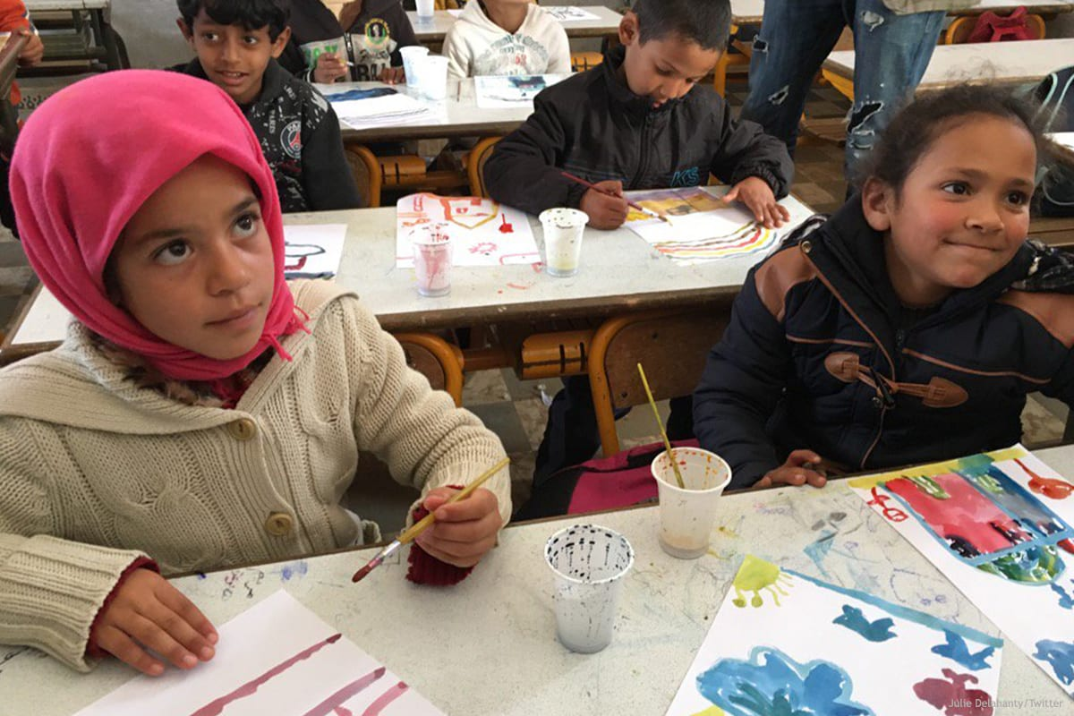 Image of Moroccan children painting in a school classroom [Julie Delahanty/Twitter]