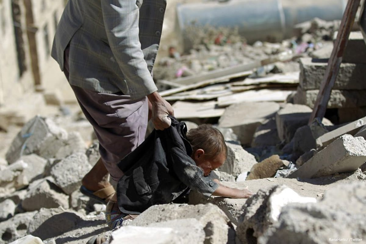 Image of a Yemeni man holding a child as he desperately searches for survivors after Saudi airstrikes hit Yemen on 11 March 2017 [RanaHarbi/ /Twitter]